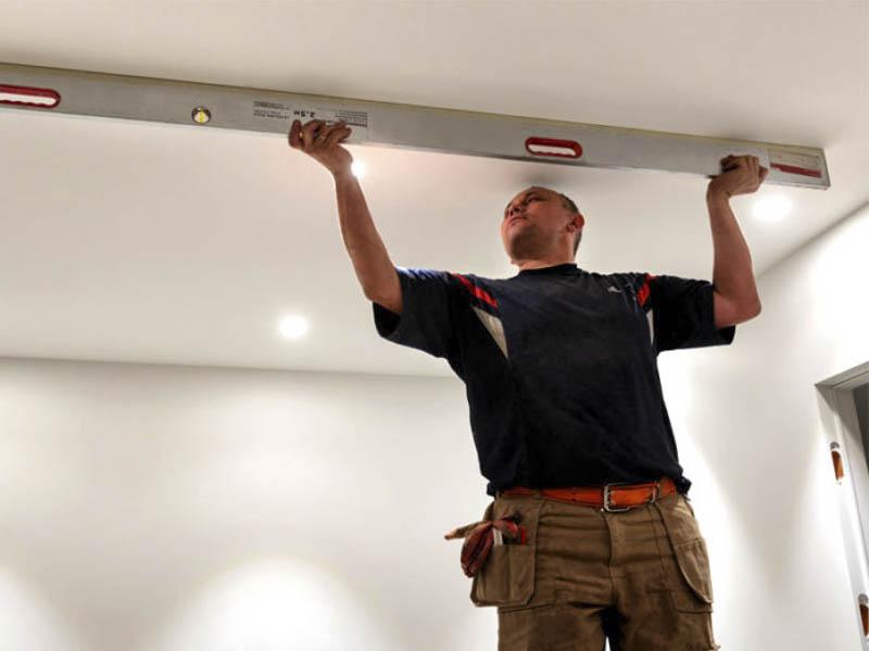 Мастер проверяет уровень потолка уровнем