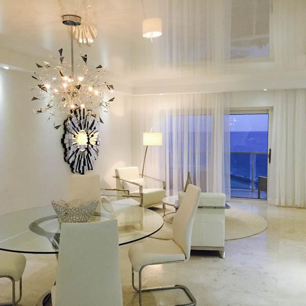 Светлая гостиная с большим окном и глянцевым натяжным потолком