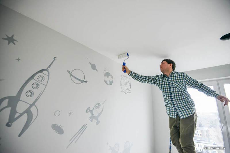 мастер красит потолок