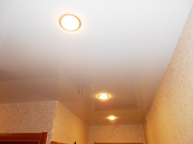 Белый глянцевый натяжной потолок в коридоре отражает цвет стен