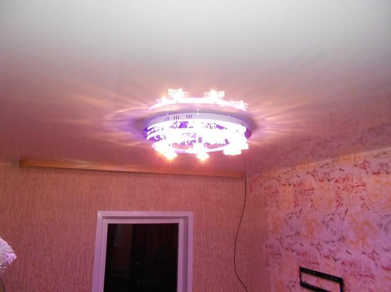Натяжной потолок в спальной комнате с карнизом для штор и люстрой