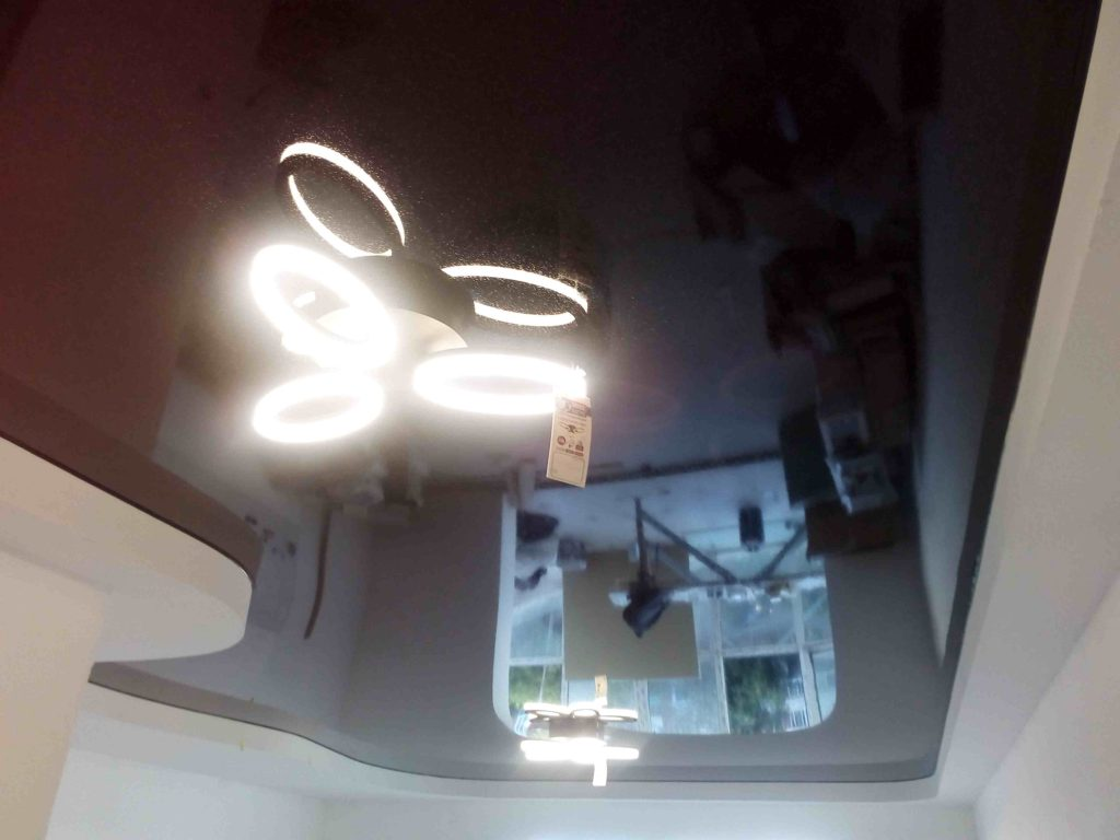 Черный цвет натяжного потолка в гостиной комнате и диодными люстрами